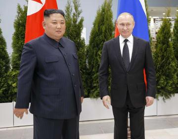 写真撮影に応じる北朝鮮の金正恩朝鮮労働党委員長(左)とロシアのプーチン大統領=25日、ロシア・ルースキー島(AP=共同)