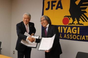 握手を交わす羽生社長(左)と大久保会長