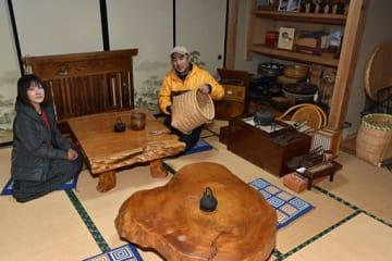 「昭和部屋」で古民具を手にする大輔さん(右)と朋恵さん=八戸市南郷