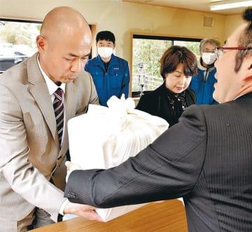 平塚さんと判明した遺骨を受け取る鈴木さん(左)