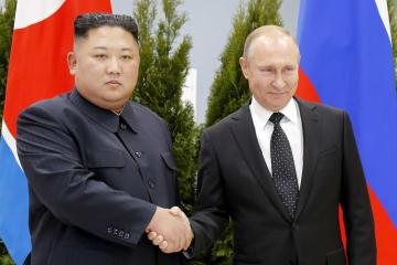 北朝鮮の金正恩朝鮮労働党委員長(左)と握手するロシアのプーチン大統領=25日、ロシア・ルースキー島(AP=共同)