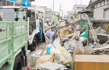 宮城県連続地震で壊れた家財などの粗大ごみを回収する作業員。東松島市野蒜の海沿いには人々の営みがあった=03年7月29日