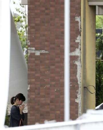 尼崎JR脱線事故から14年となり、電車がぶつかったマンションを訪れ手を合わせる女性=25日午後、兵庫県尼崎市