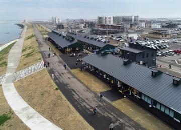 名取川の堤防沿いに建てられた商業施設「かわまちてらす閖上」=25日午後、宮城県名取市閖上