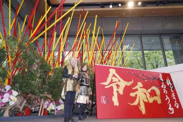 制作した生け花と書の前で写真に納まる華道家の假屋崎省吾さん(左)と書道家の青柳美扇さん=25日午後、東京都千代田区