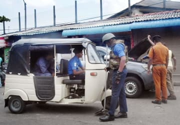 スリランカ・コロンボ市内で、通行する車両を調べる治安関係者=25日(共同)