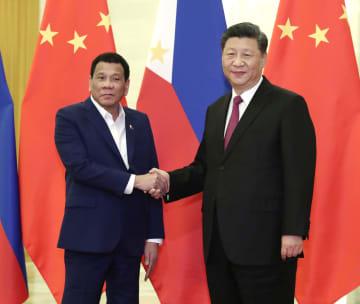 会談を前に握手を交わすフィリピンのドゥテルテ大統領(左)と中国の習近平国家主席=25日、北京の人民大会堂(共同)