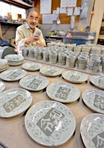 「令和」の文字がデザインされた皿や湯飲みが並ぶ、陶芸窯元「一ツ葉焼」の工房=25日午後、国富町深年