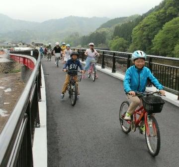 自転車に乗って第四山国川橋の渡り初めをする児童ら=25日、中津市耶馬渓町宮園