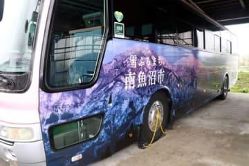 巻機山のラッピングが施されたバス。反対側には八海山が描かれる=25日、南魚沼市