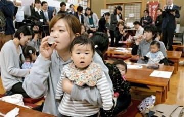 乳児用液体ミルクを試飲する母親=阿蘇市