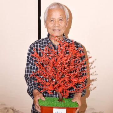 """折り鶴を貼り付けた""""折り鶴盆栽""""を持つ宇賀神さん"""