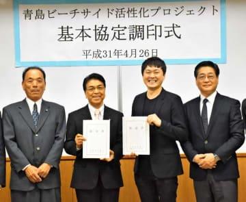 旧青島橘ホテル跡地の再開発に向けた基本協定に調印した関係者ら=26日午後、宮崎市役所