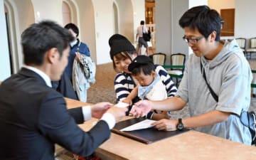 チェックインする宿泊客。10連休に備え、ホテル側は準備を進めている=26日午後、宮崎市・ANAホリデイ・インリゾート宮崎