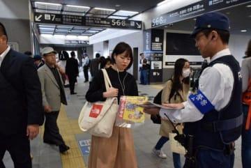 岡山駅利用者に啓発ちらしを渡しながら警戒を呼び掛ける警察官