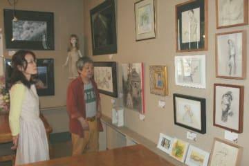 常連客による絵画や写真など約60点を展示。作品に見入る店主の内柴雅道さん(右)=日田市淡窓