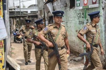スリランカ最大都市コロンボでパトロールする警察官ら=26日(ゲッティ=共同)