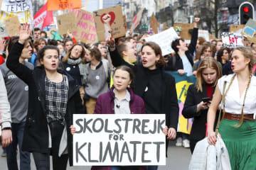 「気候のための学校ストライキ」と書かれたプラカードを持ち、若者らとデモ行進するグレタ・トゥンベリさん(手前中央)=2月、ブリュッセル(ロイター=共同)