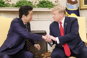 握手する安倍首相(左)とトランプ米大統領=26日、ワシントンのホワイトハウス(共同)