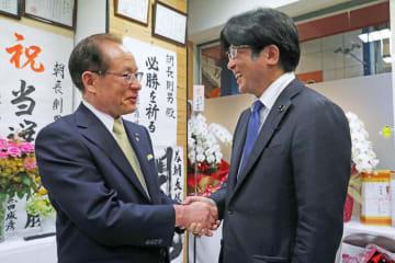 4選を確実にした朝長氏(左)を訪ね、握手する宮島氏=21日夜、佐世保市下京町の選挙事務所