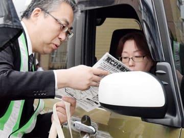 チラシを渡して情報提供を呼び掛ける警察官=26日午後4時半ごろ、熊谷市本石1丁目