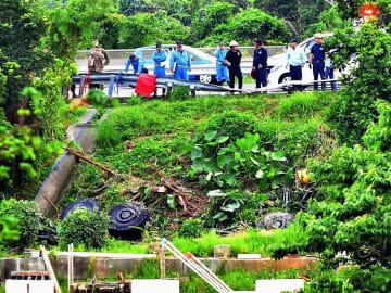 沖縄自動車道から転落した米軍中型車両(下)。タイヤを上にひっくり返っている=26日午後6時27分、うるま市石川山城(金城健太撮影)
