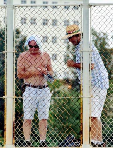 フェンスに装置を取り付ける2人の男性=26日、名護市辺野古