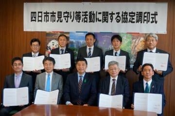 【見守り等活動に関する協定を結んだ森市長(前列中央)と各事業者代表ら=四日市市役所で】
