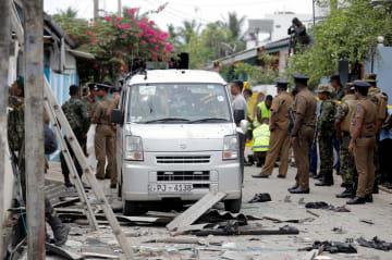 27日、スリランカ東部バティカロア近郊で、銃撃戦の現場を調べる治安当局者ら(ロイター=共同)
