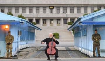 板門店の韓国側で北朝鮮側の施設「板門閣」を背に演奏する米国のチェロ奏者=27日(共同)