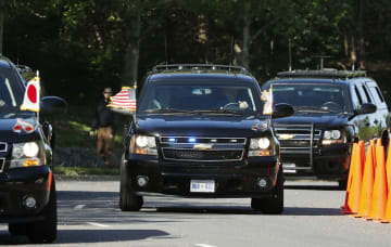 トランプ米大統領と安倍首相を乗せ、ゴルフ場に到着した車両(中央)=27日、ワシントン郊外(共同)