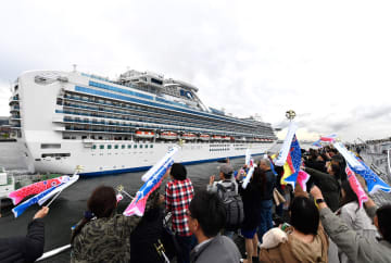 こいのぼりを掲げてダイヤモンド・プリンセスを見送り人たち=27日午後5時ごろ、横浜港大さん橋国際客船ターミナル