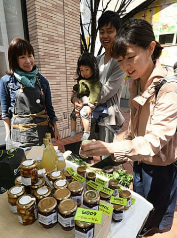 珍しい商品を品定めする買い物客(右)=27日、大阪市北区茶屋町