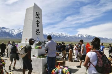 強制収容所跡地に立つ慰霊塔に花を手向ける人たち=27日、米カリフォルニア州マンザナー(共同)
