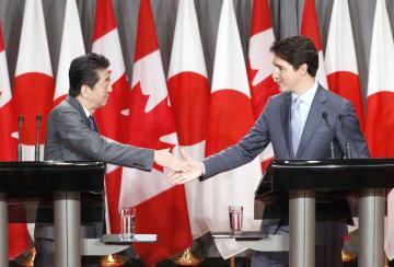 共同記者会見で握手するカナダのトルドー首相(右)と安倍首相=28日、オタワ(共同)