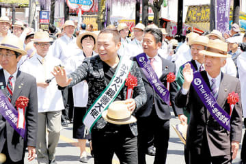 パレードに参加したはなわさん(中央)。手を振り沿道の人たちに笑顔で応えていた=春日部市中央