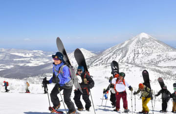青空の下、スノーボードを背負って井戸岳上部を目指すガイドツアー一行。奥に見えるのは(右から)高田大岳、雛岳=28日午前、青森市の八甲田