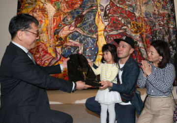 来場者1万人目となり、寺口副館長(左端)から記念品を受け取る北山さん一家