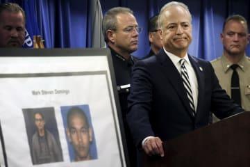 29日、米ロサンゼルスで、容疑者の写真を示し記者会見する捜査関係者ら(AP=共同)