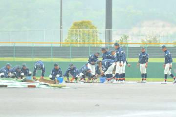 試合開始に向けてグラウンド整備する野球部員=4月30日、福井県の敦賀市総合運動公園野球場