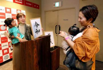 「令和」「平成」と印字した紙を手に記念撮影する来場者(撮影・大川万優)