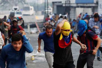 ベネズエラの首都カラカスで政権側部隊と衝突し、逃げる人々=4月30日(ロイター=共同)