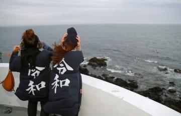 本土最東端の納沙布岬で「令和」の文字がプリントされたシャツを着て海を眺める女性。曇り空で日の出は拝めなかった=1日午前4時34分、北海道根室市