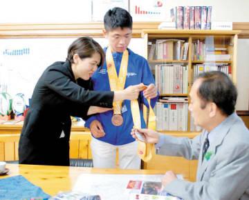 上田清司知事(右)に銅メダルを見せる沢野能文選手(中央)。左は母の玲子さん=県庁