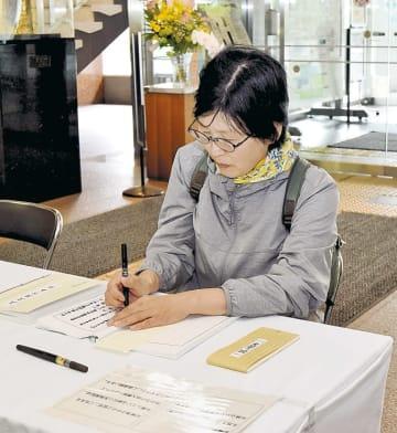 記帳簿に名前を書き込む市民=1日午前、仙台市役所本庁舎