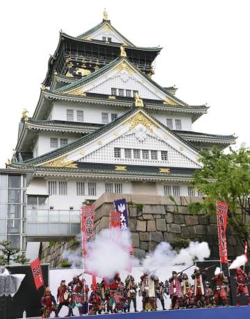 天守閣前の広場で祝砲を放つ大阪城鉄砲隊=1日午前11時11分、大阪市