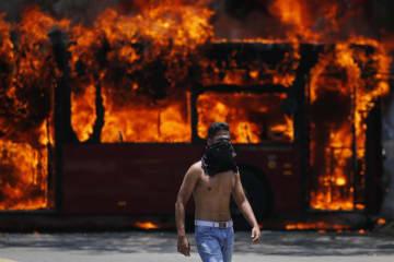 4月30日、ベネズエラの首都カラカスで炎上するバスの近くを歩く反政府派市民(AP=共同)