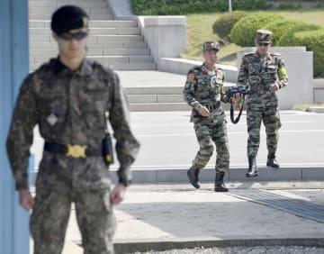 1日、板門店の共同警備区域で警備に当たる韓国軍(手前)と北朝鮮軍兵士(共同)