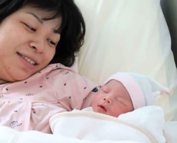 生まれたばかりの長女(右)を優しく抱き寄せ、見つめる遥さん=向日市寺戸町・ハシイ産婦人科