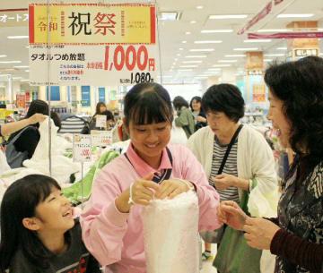 タオルの袋詰めに挑戦する買い物客=1日、大分市のイオンパークプレイス大分店